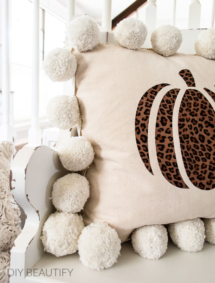 pillow with pom poms and cheetah print