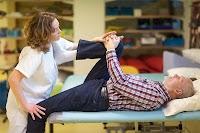 Yatan yaşlı bir adama diz çekme hareketi yaptıran bayan fizyoterapist