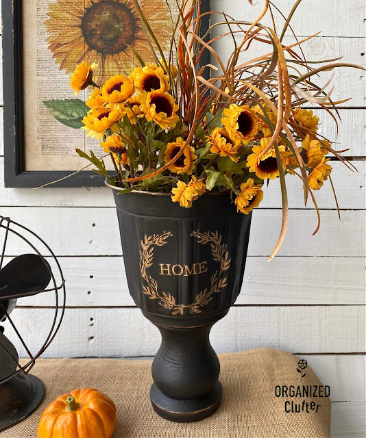 Photo of a black painted urn with sunflowers