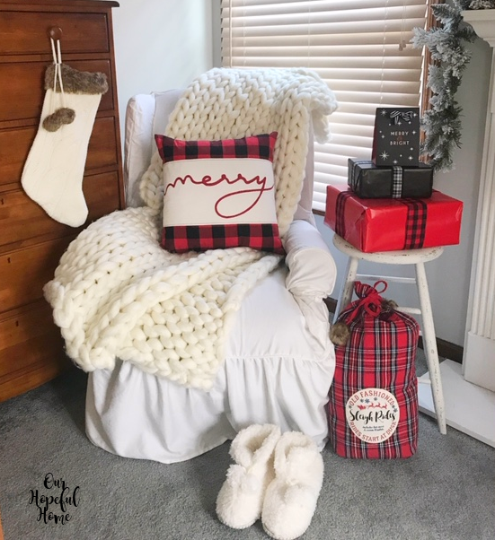 white slipcover arm chair chunky knit throw wrapped gift boxes Merry pillow white fuzzy slippers
