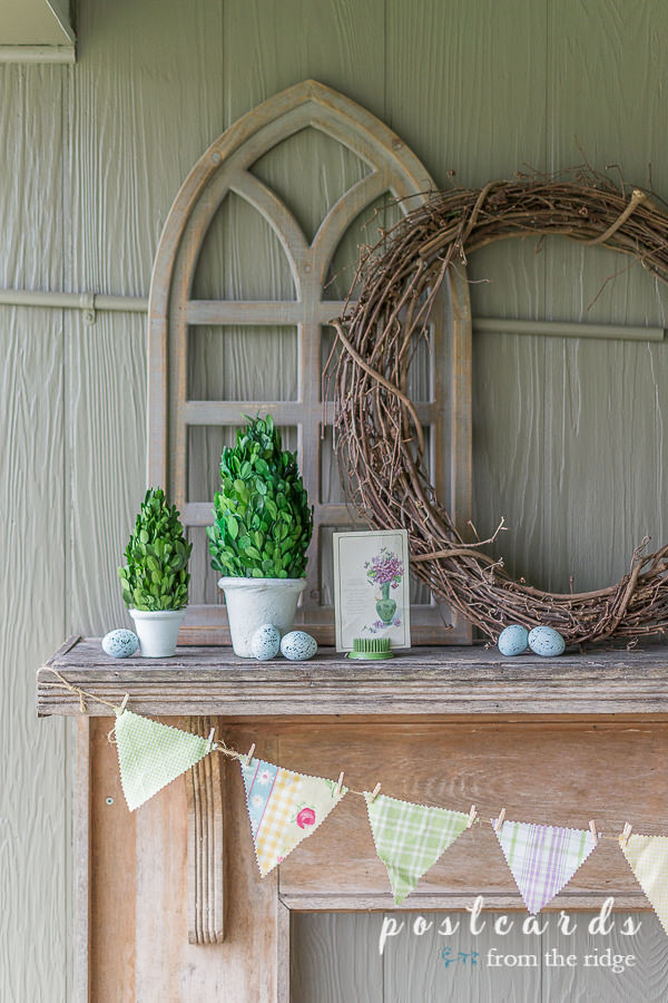 fabric banner and spring decor on rustic mantel