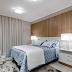 Quarto de casal com painel de madeira ripada, decor neutro e jogo de cama azul!