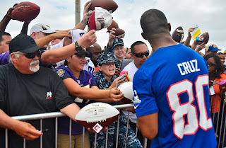 Victor Cruz, foreground, wide receiver with the New York Giants, signs autographs for U.S. Service members and their families following a National Football League (NFL) practice session at Joint Base Pearl Harbor-Hickam, Hawaii, Jan. 24, 2013
