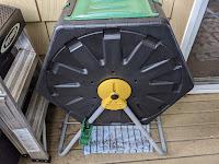 black hexagonal composter with a green sliding door