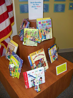 bundles of children's books tied together and displayed on tiered shelving