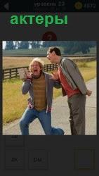 Два человека актера на дороге репетируют своих будущих персонажей. Внешне перевоплощаются согласно сценария в руках. .