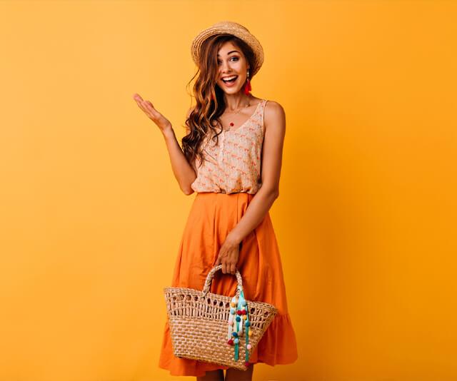 mulher sorrindo segurando uma bolsa de palha