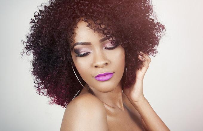 Mulher negra maquiada, cabelo cacheado, batom rosa