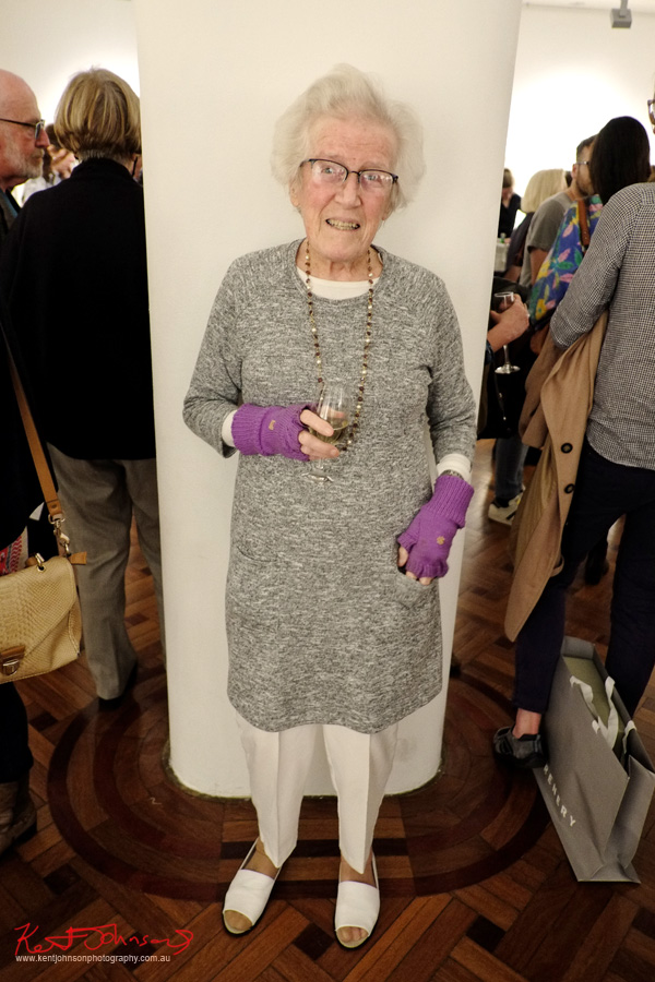 A lady wearing a long grey knit dress over white slacks and slip ons, purple finger-less gloves. Street Fashion Sydney by Kent Johnson.