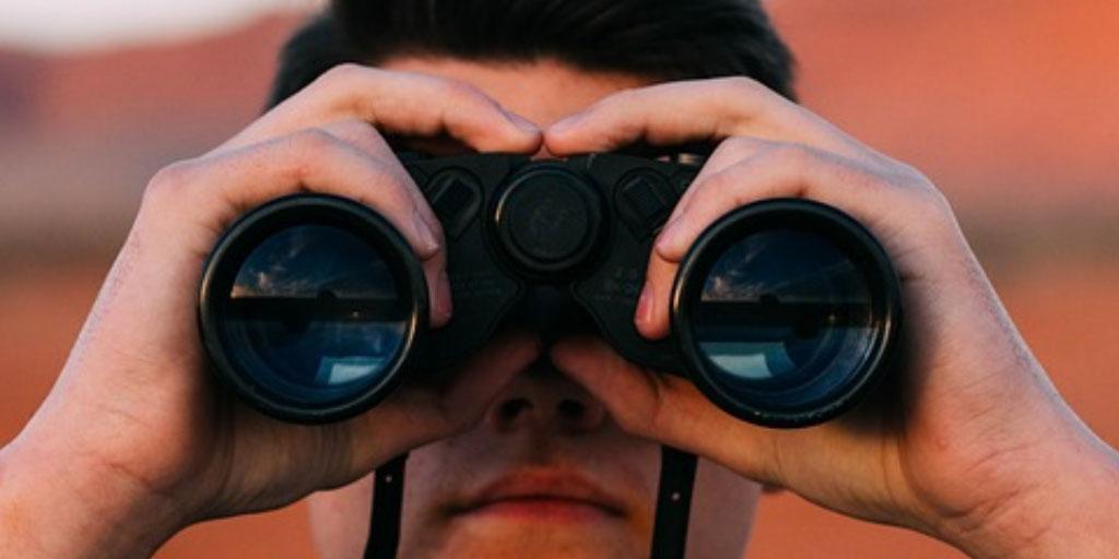 Man with binoculars looking into the future