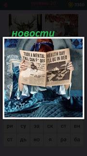 лежит женщина в постели и читает в газете новости