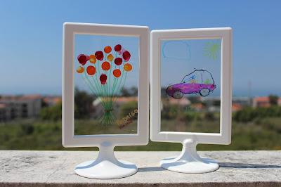duas molduras com desenhos feitos por crianças, numa superfície transparente