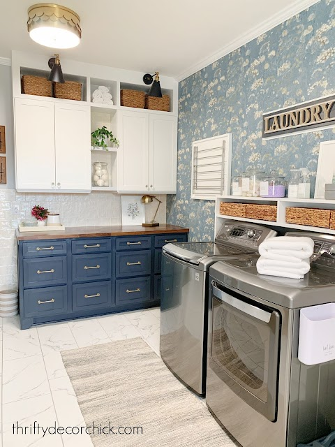 Laundry room with blue white cabinets for storage
