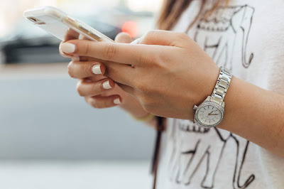 Mujer consultando el correo en el móvil en la calle