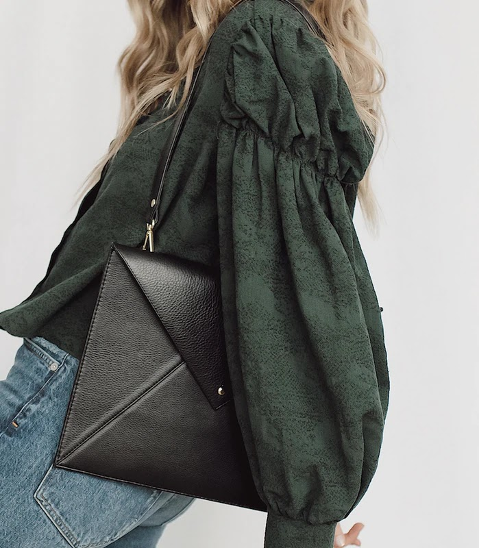 Woman holding black envelope clutch bag from TAH bags