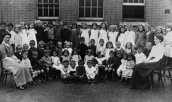 Photograph of To source: 44a Little Heath School c.1912. Infants three front rows, juniors back rows. Teachers: Miss Sammon (left) and Florence Hill (right).