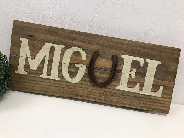 Placa em madeira de pallet com o nome Miguel e ferradura na letra U.