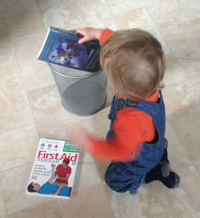 picture of a toddler putting books into a waste paper basket