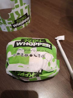 A bright green wrapped circular burger with rebel whopper in bright yellow and green font on a bright white rectangular table on a bright background