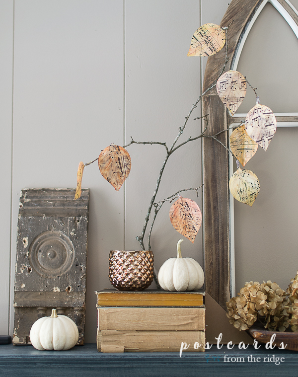 mantel with diy watercolor music sheet leaves and vintage books with baby boo pumpkins