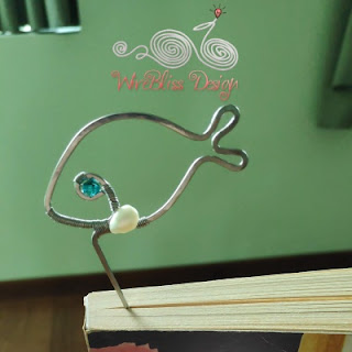 Wire wrapped fish bookmark between novel pages