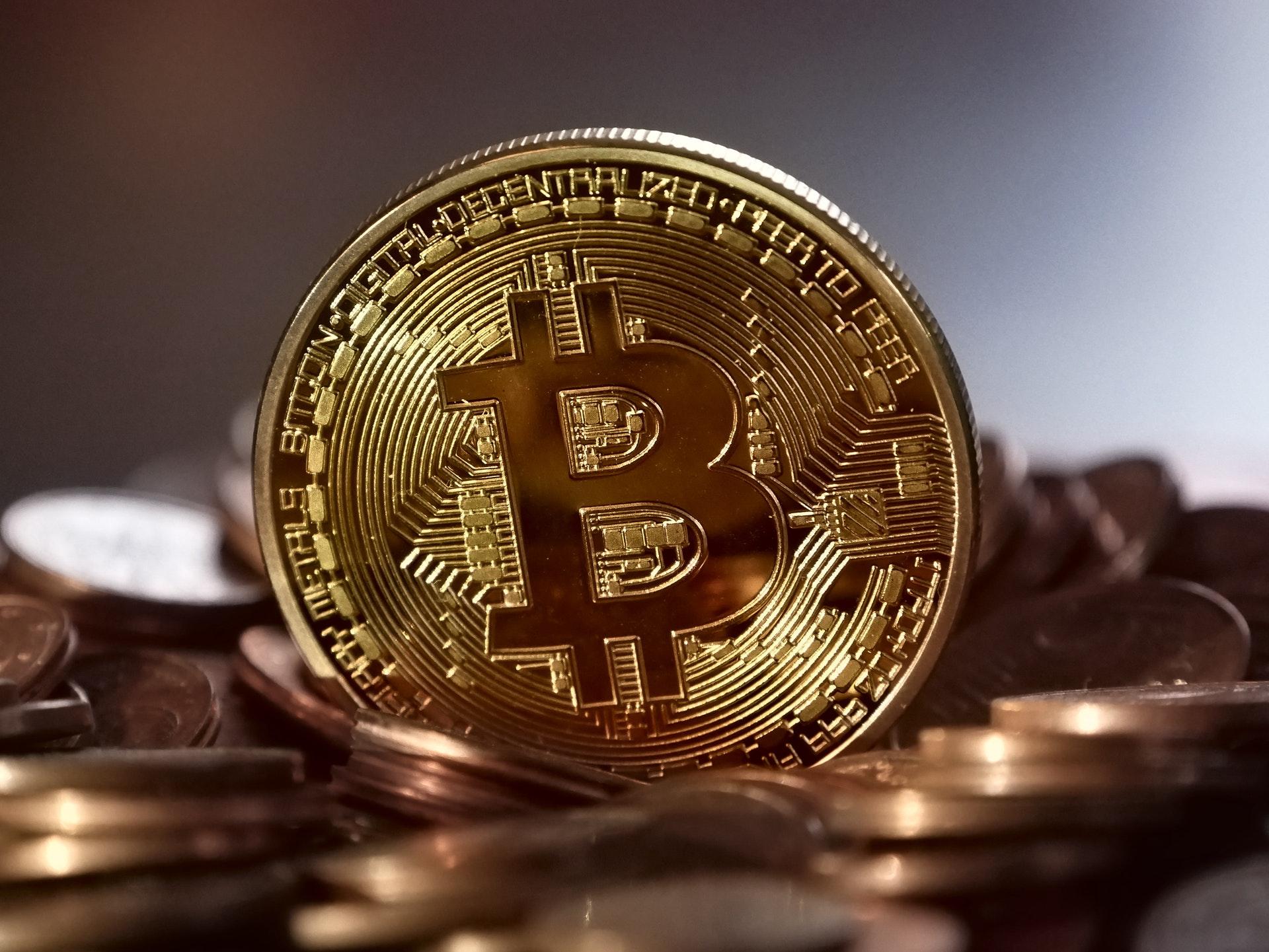 صورة لعملة البيتكوين الرقمية الافتراضية فوق مجموعة من العملات المعدنية