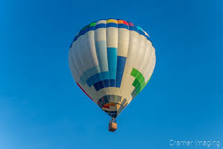 Cramer Imaging's fine art photograph of a white and multi-colored hot air balloon floating over a field in Panguitch Utah with a blue sky
