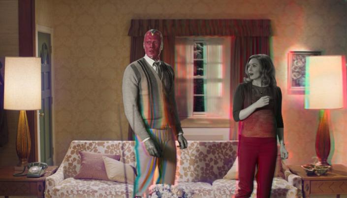 Imagem: Visão e Wanda em roupas de época, na sala de sua casa, com um abajur, um sofá e etc. onde tudo que estava antes em preto e branco agoraestá se tornando colorido.