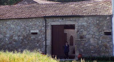 mulher encostada numa porta de uma casa rural