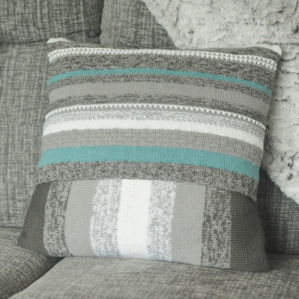 back of blue and grey knitted cushion on a grey sofa