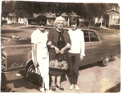 unidentified young women with 1960s hairstyles with Leona Grant of Alameda CA in front of car in driveway