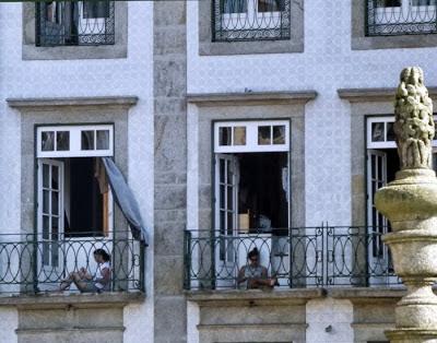 duas senhoras sentadas nas varadas de edificio do Porto