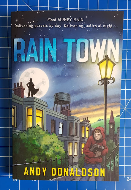 Cover of Rain Town by Andy Donaldson showing night time scene in a town street