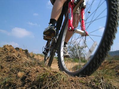 Närbild framifrån på terrängscykel som kör på grusstig.