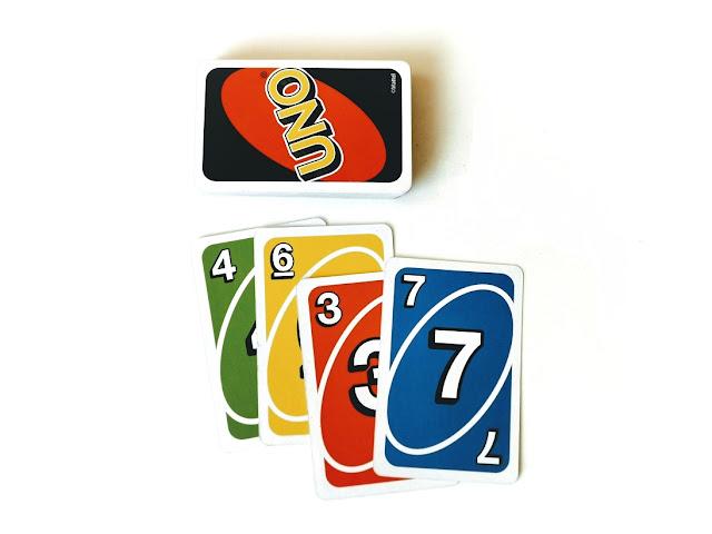 na zdjęciu leży stos zakrytych kart uno a obok na stosie kart odrzuconych leża cztery karty których suma daje wartość dwadzieścia