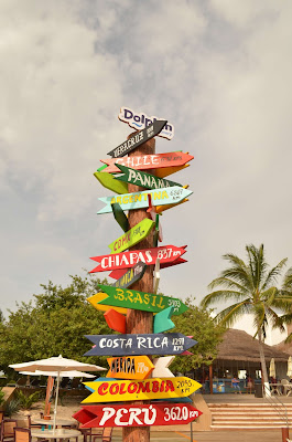Palo con carteles de diferentes paises y la distancias que están desde México