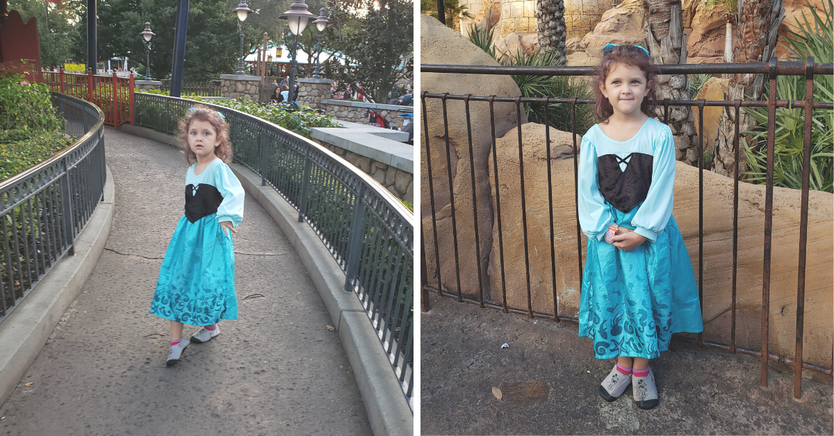 Two photos of a curly haired little girl in a blue and black dress. The photo on the left, she looks concerned and upset. The photo on the right, she is happy and standing in front of Ariel's castle.