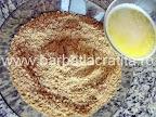Tort cu bezea crema de ciocolata preparare reteta blat - amestecam biscuitii cu untul topit