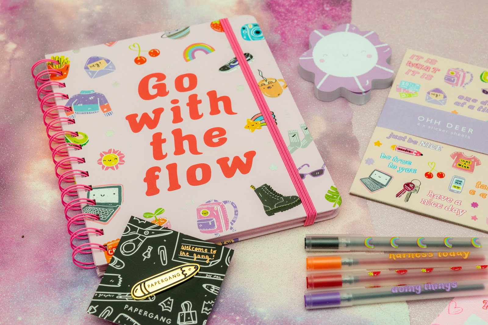 A flat lay of a spiral bound notebook with the phrase 'go with the flow' on the front, purple flower shaped post-it notes and a packet of doodle stickers.