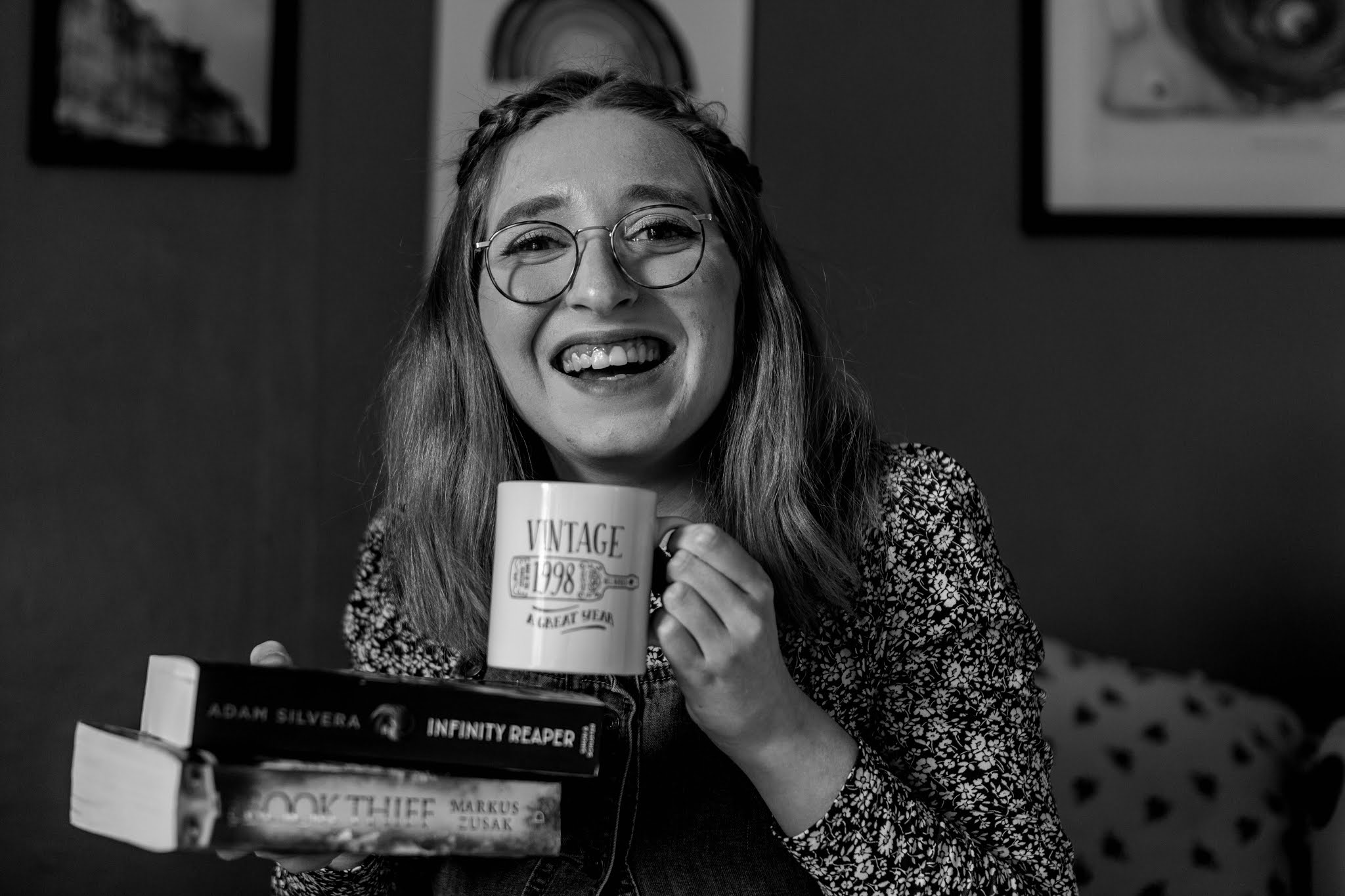 black and white photo of girl smiling while holding book stack and white mug