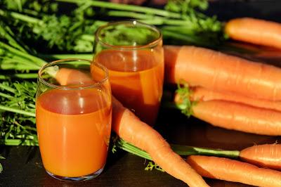Sok z marchwi w dwóch szklankach obok marchewek
