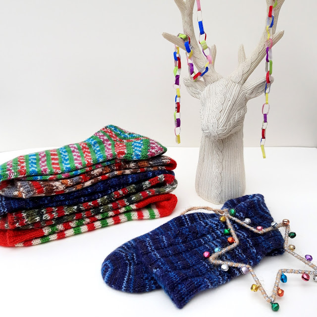 A stack of multi-coloured socks on a white background with a reindeer ornament and one sock in the foreground