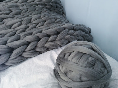grey blanket next to ball of yarn