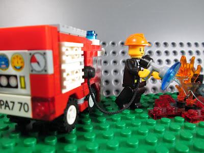 Bombeiro minifigura LEGO apaga fogo.