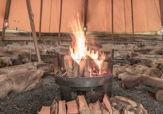 a roaring wood fire inside a sami lavvu (or yurt) with lots of seating