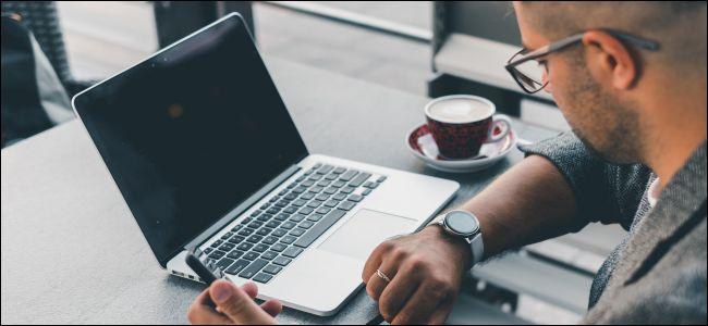 رجل على طاولة في مقهى ينظر إلى ساعته ويفتح أمامه جهاز الكمبيوتر المحمول الخاص به.