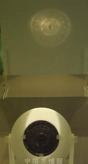 A luz na superfície do espelho é refletida e refratada de tal forma que o bronze parece transparente