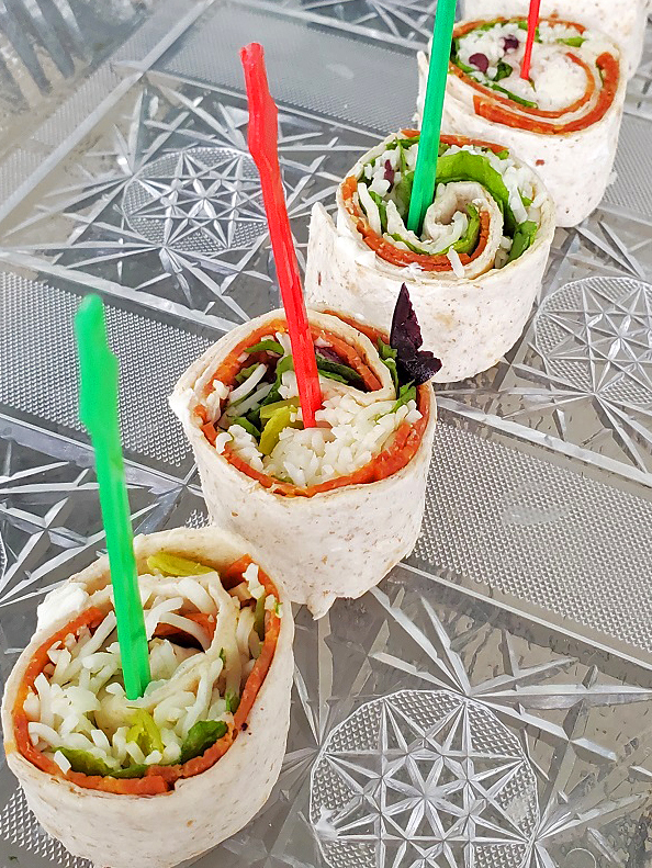 these are cut tortilla that have been rolled with a filling to make an appetizer with the wrap. It has shredded mozzarella, pepperoni, peppers and olives in side with arugula and tomato sauce with cream cheese