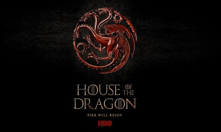 """Imagem:  símbolo feito de metal, um dragão de três cabeças que representa a Casa Targaryen. O símbolo é circular e as asas e a cauda do Dragão contornam como se fosse a borda do círculo. Abaixo está escrito """"House of the Dragon"""" """"Fire will reign"""", """"hbo"""". Fundo preto."""