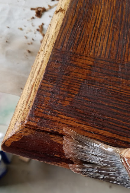 Paint brush used to apply Citristrip to wooden stained tabletop.